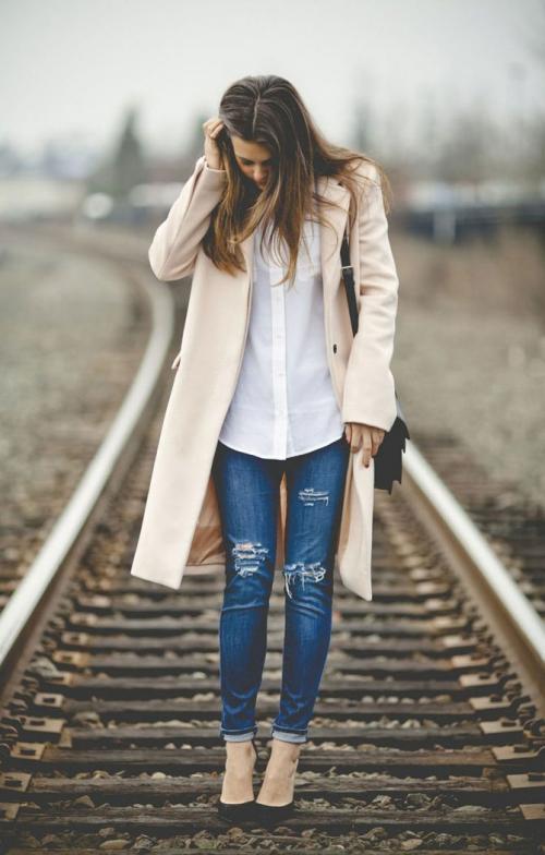 Девушка в пальто и рваных джинсах