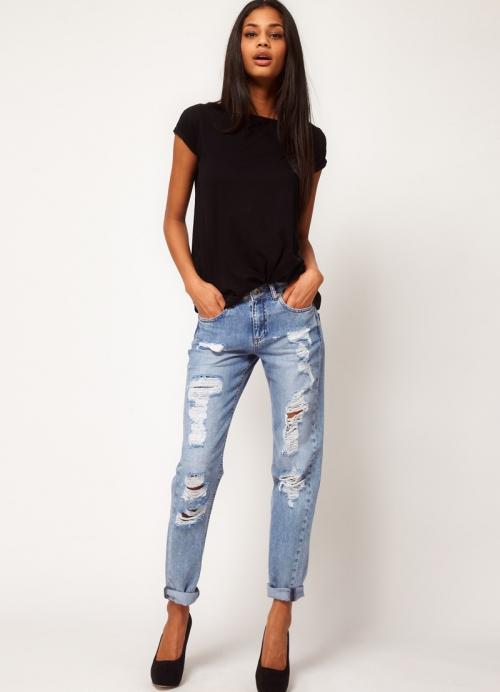 Девушка в черной блузке и рваных джинсах