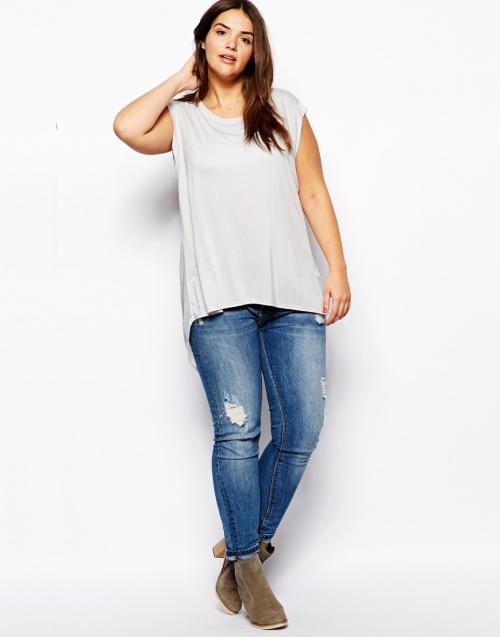 Девушка в серой майке и джинсах с потертостями